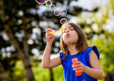 Beautiful child blowing bubbles Stock Photo