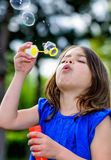 Beautiful child blowing bubbles Royalty Free Stock Image