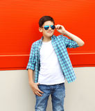 Beautiful child boy wearing a sunglasses and shirt over red Royalty Free Stock Photography