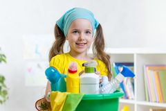 Beautiful child cleaning room. Little girl holding bowl full of bottles with disinfectant. Beautiful child cleaning room. Little kid holding bowl full of royalty free stock photography