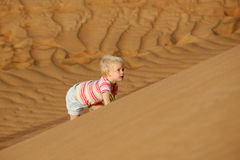 Child climbing sand dune. Beautiful child climbing steep sand dune Stock Photo
