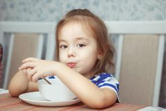 Beautiful Child eating dish at table stock photo