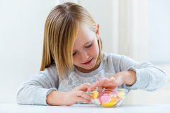 Beautiful child eating sweets at home. Stock Images