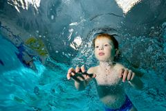 A beautiful child is engaged in sports. Swims underwater in the pool on a blue background and looks forward. Portrait. Shooting underwater from the bottom Royalty Free Stock Photos