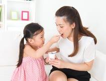 Beautiful child feeding mother yogurt. Eating yogurt. Happy Asian family eating yoghurt at home. Beautiful child feeding mother, healthcare concept Stock Photo