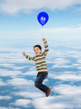 Beautiful child flying on the sky with a balloon Stock Photo