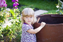 The beautiful child at a garden barrel Royalty Free Stock Photos