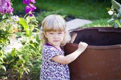 The beautiful child at a garden barrel Royalty Free Stock Photos