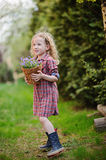 Beautiful child girl with basket of bluebell flowers in spring garden Stock Photos
