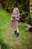 Beautiful child girl with basket of bluebell flowers in spring garden Royalty Free Stock Photo