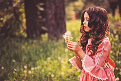 Beautiful child girl dressed as fairytale princess playing with blow ball in summer forest Royalty Free Stock Image