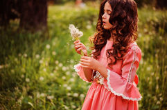 Beautiful child girl dressed as fairytale princess playing with blow balls in summer forest Royalty Free Stock Photo