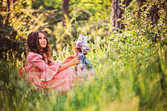 Beautiful child girl dressed as fairytale princess playing with doll in summer forest Stock Images