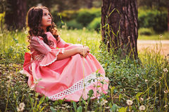 Beautiful child girl dressed as fairytale princess sitting in summer forest Royalty Free Stock Photos