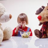 Beautiful child girl eating fruit salad with a good friends: ted royalty free stock images