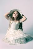 Beautiful child girl in elegant dress and hat. Stock Photography