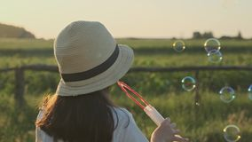 Beautiful child girl in a hat blowing soap bubbles