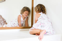 Beautiful child girl looking at herself in mirror at home Stock Images