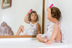 Beautiful child girl looking at herself in mirror at home Royalty Free Stock Image