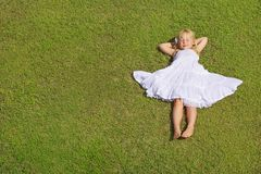 Beautiful Child Girl Lying on the Green Grass, top view stock image