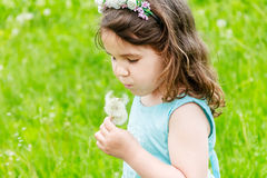 Beautiful child girl in park. Happy kid having fun outdoo. Beautiful child girl with dandelion flower in spring park. Happy kid having fun outdoors Stock Images