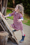 Beautiful child girl with rustic wooden planks in spring garden Stock Photos