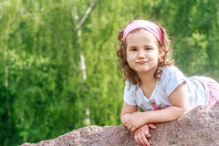 Beautiful child girl in spring park. Happy kid having fun. Outdoors Stock Image