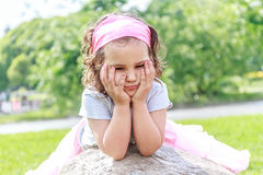 Beautiful child girl in spring park. Happy kid having fun. Outdoors Stock Photo