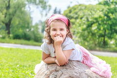 Beautiful child girl in spring park. Happy kid having fun outdoors Stock Photos