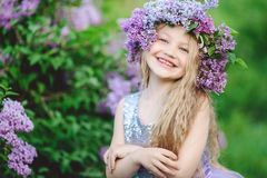 Beautiful child girl with wreath of lilac flowers. Cute beautiful little smiling blonde girl with long hair is wearing wreath made from lilac flowers Royalty Free Stock Photos