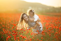 Beautiful child girl with young mother are having fun in field of poppy flowers over sunset lights. Beautiful couple mother and cute daughter are walking in stock photos