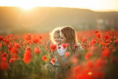 Beautiful child girl with young mother are wearing casual clothes in field of poppy flowers over sunset lights. Beautiful couple mother and cute daughter are royalty free stock photo