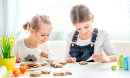 Child girl decorating Easter cookies royalty free stock images