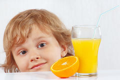 Beautiful child with a glass of fresh juice and orange Royalty Free Stock Photos
