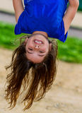 Beautiful child hanging upside and laughing. Beautiful child hanging upside, laughing, with greenery in the background Stock Images