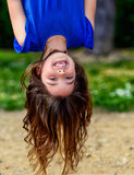 Beautiful child hanging upside and laughing. Beautiful child hanging upside, laughing, with greenery in the background Stock Photos