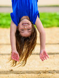 Beautiful child hanging upside and laughing. Beautiful child hanging upside, laughing, with greenery in the background Stock Photography