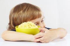 Beautiful child hugging a bowl of millet porridge favorite Stock Images
