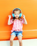 Beautiful child listens to music in headphones over colorful orange background Stock Images