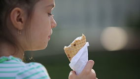 Beautiful child little girl eating ice cream on the street. stock video footage