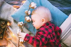 Beautiful child lying on the bed on pillows and plaid with a branch of cotton. On a background garlands Stock Images