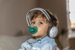 A beautiful child with a pacifier is listening to music with large headphones. In the living room of his home royalty free stock photo