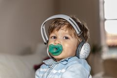 A beautiful child with a pacifier is listening to music with large headphones. In the living room of his home stock photos