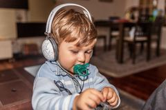 A beautiful child with a pacifier is listening to music with large headphones. In the living room of his home royalty free stock images