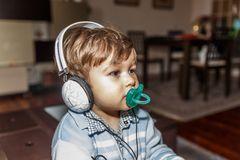 A beautiful child with a pacifier is listening to music with large headphones. In the living room of his home royalty free stock photography
