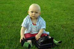 Beautiful child with phone on the green grass Stock Image