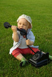 Beautiful child with phone on the green grass Royalty Free Stock Photos