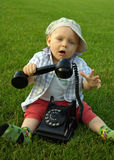 Beautiful child with phone on the green grass Royalty Free Stock Images