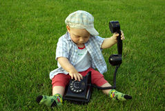 Beautiful child with phone in hand on the green gr Royalty Free Stock Image