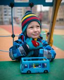 Beautiful child on the playground area in the winter stock images